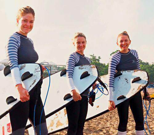 Three smiling girls at Ocean Soul Retreat with surfboards, surf lessons for women, Bali wellness yoga and surfing retreat, learn to surf in Seminyak