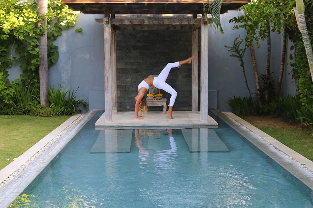 Woman arches back for Yoga position, in Seminyak Bali, Hatha, Iyengar, Vinyasa, Pool at Ocean Soul Retreat