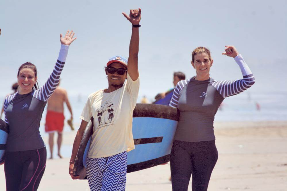 Two women with their surf Bali instructor, happy and fist pumping, womens surf retreat