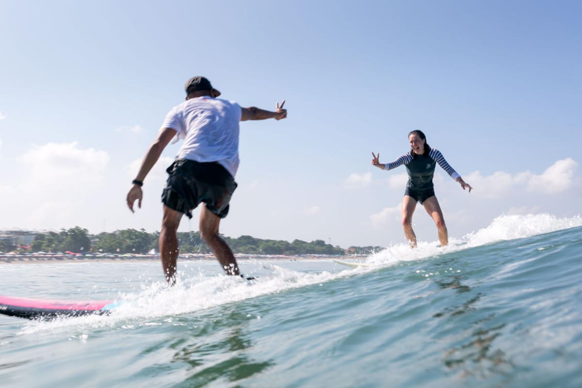 Women Surfing Instruction in Bali, female student giving happy peace sign to teacher while surfing