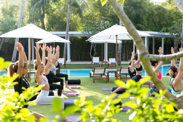 View through the trees of women doing Yoga on he lawn and pool-side