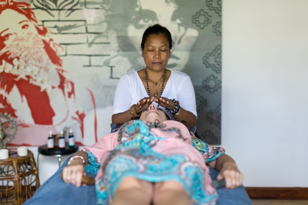 Woman enjoying holistic healing session, balinese practitioner placesclaming hands on her head